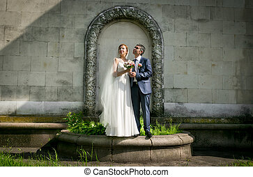 bride and groom posing at park under floral arch