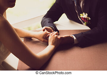 toned photo of bride and groom holding hands at restaurant -...