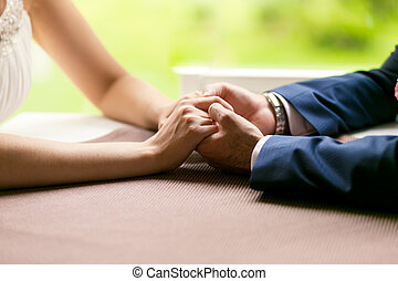 Closeup of bride and groom holding hands on table at...