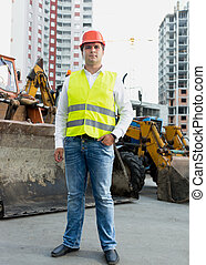 Businessman in safety jacket and hardhat posing next to...