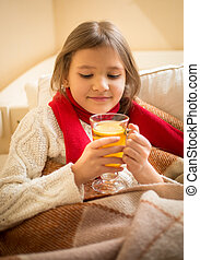 cute girl lying in bed and holding cup of tea with lemon -...