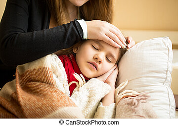 Closeup of caring mother holding head on sick daughter...