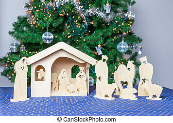 Wooden christmas stable with bible figurines and tree on...