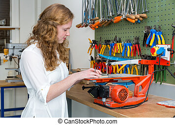 Dutch teenage girl operating electric jigsaw in classroom -...