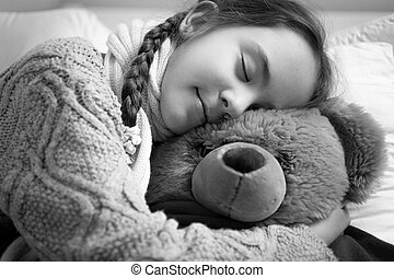 black and white portrait of cute dreaming girl hugging teddy...