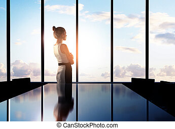 businesswoman thinking in office and looking to sky
