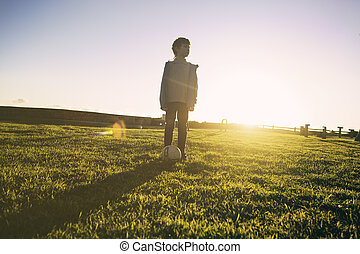 Portrait of a boy staying on green grass with soccer ball -...