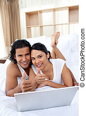 Smiling couple lying on the bed
