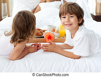 Close-up of siblings bringing breakfast to their parents