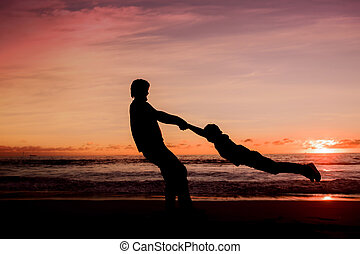 Silhouettes of father spinning his son around on sunset on...
