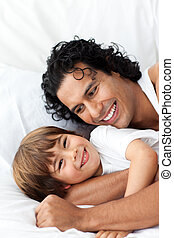 Little boy and his father on a bed