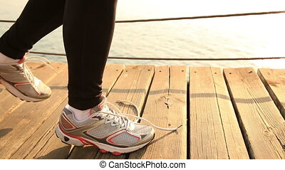 healthy lifestyle sports woman tying shoelace on wooden...