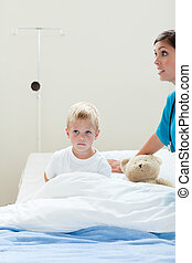 Portrait of a sick little boy on a hospital bed with a teddy...