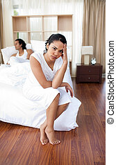 Upset lovers sitting on the bed separately after a row