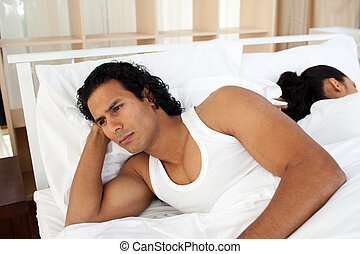 Upset man in bed sleeping separate of a woman after having...