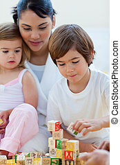 Mother and children playing with alphabetics blocks in the...