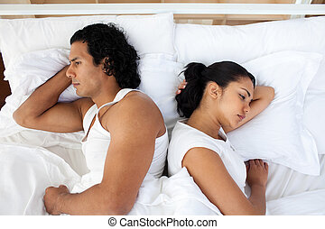 Couple lying separately in bed after having a fight