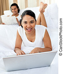 Young woman using a laptop smiling at the camera