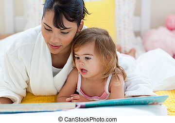 Attentive mother reading with her little girl