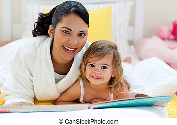 Portrait of a smiling mother and her daughter reading...