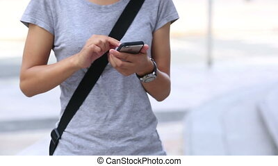 young asian woman use cellphone on city