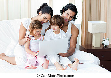 Young family using a credit card to shop online at home