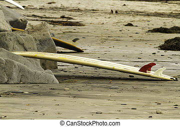 Surfboard leaning on rocks at beach - Surfboard leaning on...
