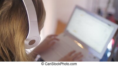 Woman in headphones using laptop - Woman in white headphones...
