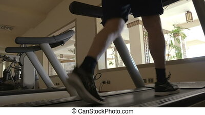 Stepping on treadmill in the gym - Low angle shot of man...