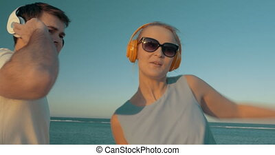 A lively dance of young people in headphones outdoor - Young...