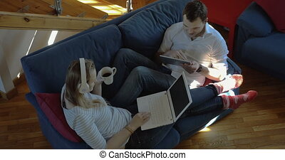 Man and woman at home using pad and laptop
