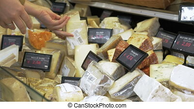 Great assortment of cheese in the shop - Woman looking over...