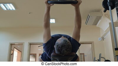Exercise with lifting weight plate lying on bench - Low...