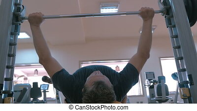 Strong man working on bench press - Low angle shot of a man...