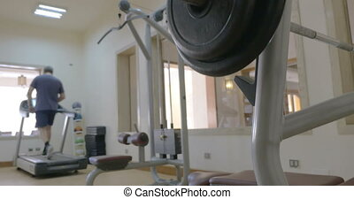 Sportsman putting disk weight on the barbell in gym