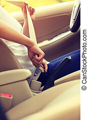 woman driver buckle up the seat belt before driving car -...