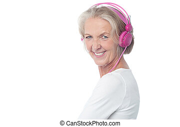 Hearing music is my best hobby - Aged happy woman listening...
