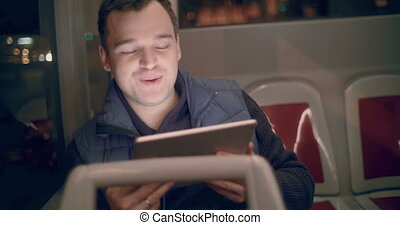 Man with tablet PC having a video chat in the bus - Happy...