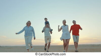 Enjoable family walk on the beach - Five members of family...
