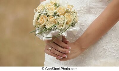 Wedding Bouquet - Bride standing in a field with a wedding...
