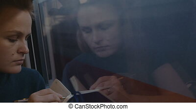 Woman taking notes or drawing in train - Timelapse of young...