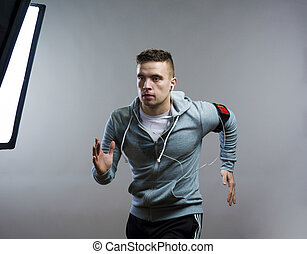 Runner in a studio - Young sportsman running. Studio shot on...