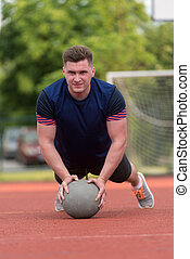 Young Man Exercising Push-Ups On Medicine Ball Outdoor -...