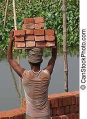 Loading bricks - A man carries 16 bricks on his head at...