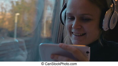 Entertainment with music and phone in the train - Woman...