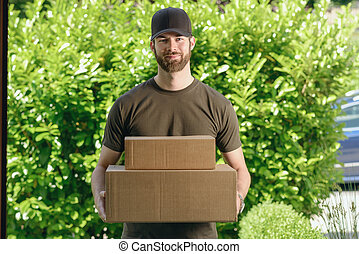 Handsome delivery man with two cardboard boxes - Handsome...