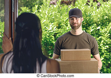 Woman answering the door to a deliveryman - Woman answering...