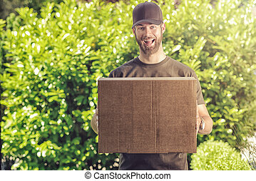 Cute guy with a happy grin making a delivery - Cute bearded...