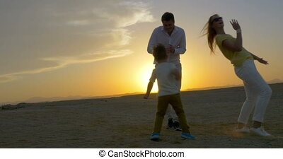 Parents and Son Dancing at Sunset - Steadicam shot of a...