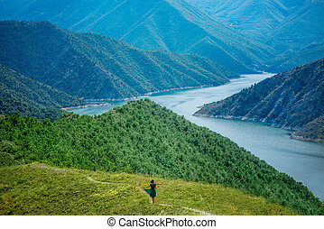 Woman walking on the mountains - Woman in green dress and...